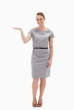 Donna sorridente in un vestito che presenta qualcosa Immagini Stock