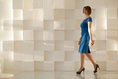 Donna sorridente in vestito blu che cammina contro la parete moderna con il portafoglio a disposizione Immagini Stock