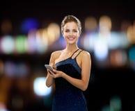 Donna sorridente in vestito da sera con lo smartphone Immagine Stock Libera da Diritti