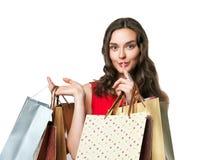 Donna sorridente in vestito rosso con i sacchetti della spesa Fotografia Stock Libera da Diritti