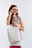 Donna sorridente in vetri che tengono borsa bianca di compera Fotografie Stock