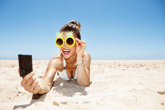 Donna sorridente in vetri dell'ananas che prendono selfie alla spiaggia sabbiosa Fotografie Stock Libere da Diritti
