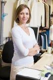 Donna a sorridere della memoria di vestiti Immagine Stock