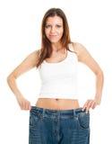 Donna sottile che tira i jeans surdimensionati Fotografia Stock