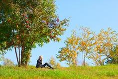 Donna sotto l'albero di cenere della montagna Immagini Stock
