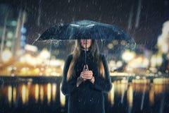 Donna sotto pioggia con l'ombrello nero Fotografie Stock Libere da Diritti