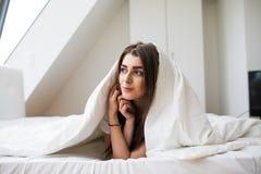 Donna sotto un piumino nella sua camera da letto immagini stock libere da diritti
