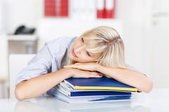 Donna sovraccarica che riposa sui raccoglitori dell'ufficio Immagini Stock Libere da Diritti