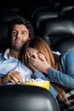 Donna spaventata che si appoggia uomo nel teatro del cinema Immagine Stock