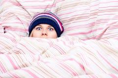 Donna spaventata che si nasconde in duvet Fotografie Stock