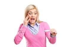 Donna spaventata che tiene una prova di gravidanza positiva Fotografie Stock
