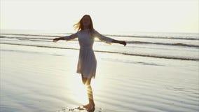 Donna spensierata che fila intorno sulla riva di mare bagnata video d archivio