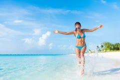 Donna spensierata di vacanza di divertimento della spiaggia che spruzza acqua Immagine Stock