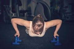 Donna spinta-UPS sul pavimento, lei nel contare sui blocchetti di yoga mentre spingendo corpo verso l'alto con la concentrazione  fotografia stock