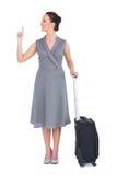 Donna splendida allegra con la valigia che indica il suo dito su Fotografia Stock Libera da Diritti