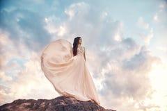 Donna splendida castana nelle montagne al tramonto ed al cielo blu con le nuvole La donna esamina la distanza in un bianco lungo fotografie stock libere da diritti