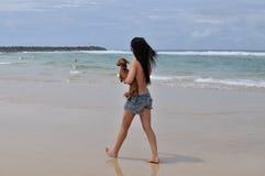 Donna splendida che cammina lungo la spiaggia con il suo cane Fotografie Stock