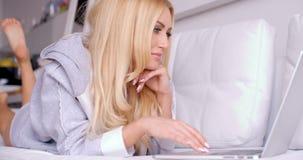 Donna splendida che si trova sullo strato occupato con il suo computer portatile stock footage