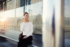 Donna splendida con il sorriso sveglio che ha conversazione piacevole sullo Smart Phone mentre lei trasporto pubblico aspettante  Immagine Stock Libera da Diritti