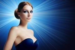 Donna splendida con trucco di sera su un fondo blu Immagine Stock Libera da Diritti