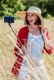 Donna splendida 50s che fa un selfie sul telefono cellulare sul bastone Fotografie Stock Libere da Diritti