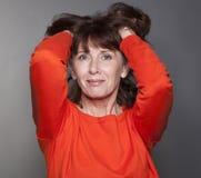 Donna splendida 50s che tocca i suoi capelli per soddisfazione Fotografie Stock Libere da Diritti