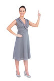 Donna splendida sorridente in vestito di classe che indica il suo dito su Immagine Stock