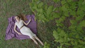Donna splendida in vestito bianco che si trova sulla coperta e sulla posa archivi video