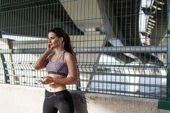 Donna sportiva all'aperto che prende una rottura durante l'allenamento fotografia stock