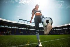 Donna sportiva atletica in abiti sportivi con pallone da calcio sullo stadio fotografie stock libere da diritti