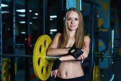 Donna sportiva attraente che si esercita con il bilanciere in palestra La bella ragazza di forma fisica che riposa dopo l'allenam Immagini Stock
