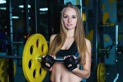 Donna sportiva attraente che si esercita con il bilanciere in palestra La bella ragazza di forma fisica che riposa dopo l'allenam Immagine Stock Libera da Diritti