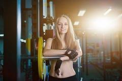 Donna sportiva attraente che si esercita con il bilanciere in palestra La bella ragazza di forma fisica che riposa dopo l'allenam Fotografia Stock