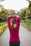 Donna sportiva che allunga armi all'aperto in autunno Fotografia Stock