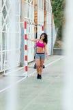 Donna sportiva che allunga armi prima dell'allenamento all'aperto del trx Fotografia Stock