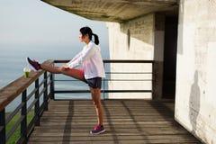 Donna sportiva che allunga e che si esercita verso il mare Immagini Stock