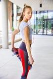 Donna sportiva che allunga gamba prima dell'correre sul sentiero per pedoni Fotografia Stock