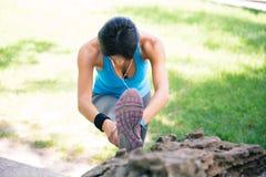 Donna sportiva che allunga le gambe in parco Immagini Stock