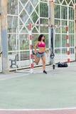 Donna sportiva che allunga le gambe prima dell'allenamento all'aperto del trx Fotografia Stock