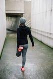 Donna sportiva che allunga prima dell'correre Immagine Stock