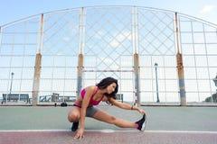 Donna sportiva che allunga tendine del ginocchio prima dell'allenamento di forma fisica Fotografia Stock