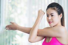 Donna sportiva che fa allungamento del braccio Immagini Stock