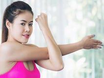 Donna sportiva che fa allungamento del braccio Fotografia Stock Libera da Diritti