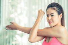 Donna sportiva che fa allungamento del braccio Fotografie Stock
