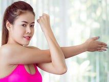 Donna sportiva che fa allungamento del braccio Fotografia Stock
