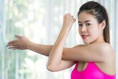 Donna sportiva che fa allungamento del braccio Fotografie Stock Libere da Diritti