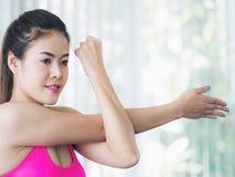 Donna sportiva che fa allungamento del braccio Immagine Stock