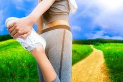 Donna sportiva che fa allungamento della gamba Fotografie Stock Libere da Diritti