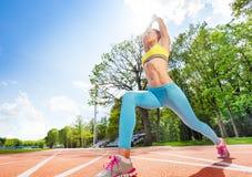Donna sportiva che fa allungando esercizio allo stadio Immagini Stock