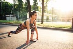 Donna sportiva che fa allungando gli esercizi in parco Immagine Stock Libera da Diritti